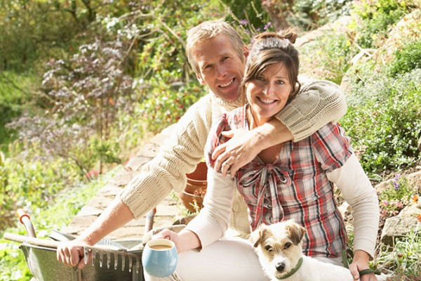 BRE32P Couple With Dog Having Coffee Break Whilst Working Outdoors In Garden